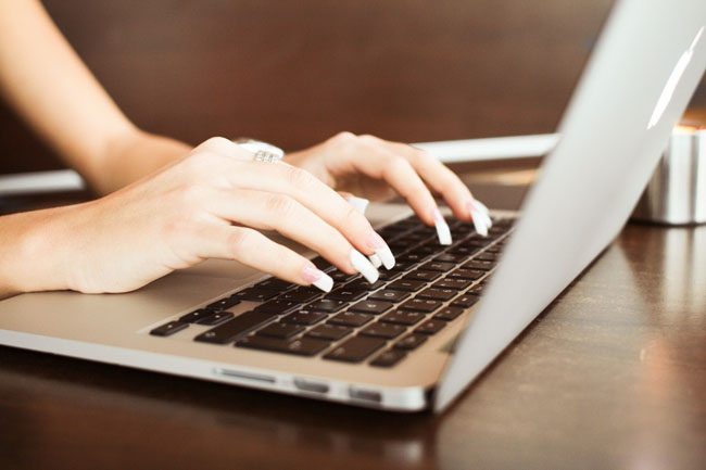 detail-of-girls-hands-typing-on-macbook