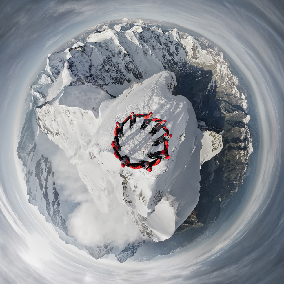 Nine Mountain Climbers atop a Swiss Mountain Peak