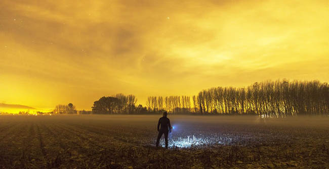 man standing in the field at night